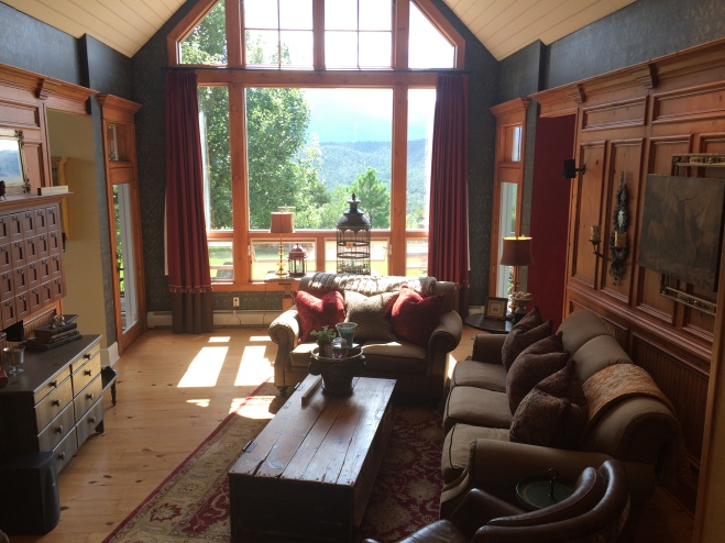 Living Room with custom woodwork and picture window featuring Fishers Peak