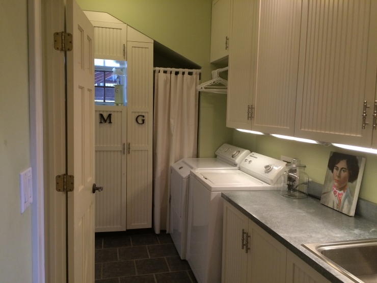 Laundry Room off of Foyer features enclosed storage as well as a Powder Room